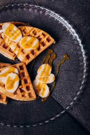 Waffles with bananas on a concrete gray background.