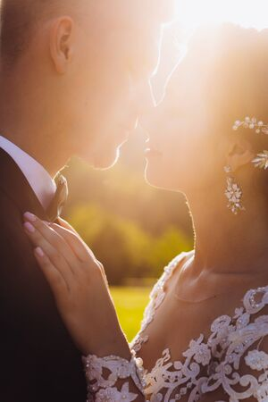 Kiss love bride and groom. Happy together against the background of green grass and a lake at sunset.