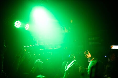 People at a concert in the light of spotlights. rock concert. 免版税图像