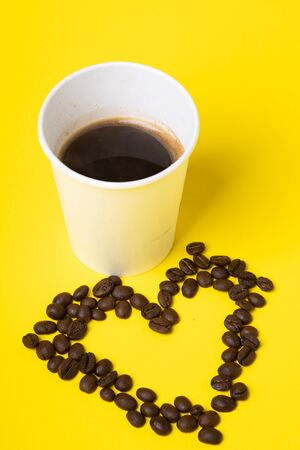 White Cup with coffee on yellow background and coffee beans in heart shape. Foto de archivo