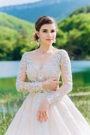 Die Braut in einem weißen Hochzeitskleid auf dem Hintergrund des grünen Grases und des Sees.