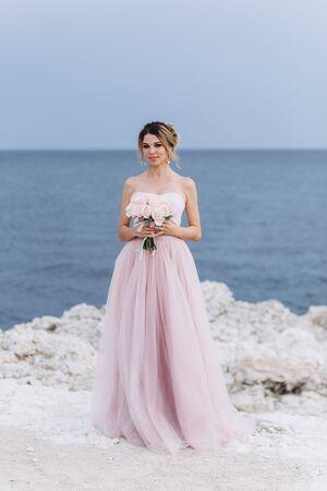 Porträt einer jungen schönen Braut mit einem Rosenstrauß nahe dem Meer. Standard-Bild