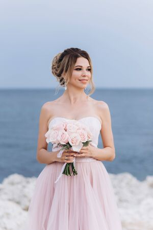 Portrait of a young beautiful bride with a bouquet of roses near the sea.