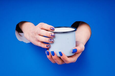 Blue matte manicure on a blue background with round blue glasses. Women's hands.