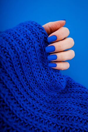 Blue matte manicure on a blue background with round blue glasses.