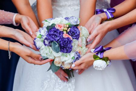 Wedding bouquet in the hands of the bride. Many hands of girl.