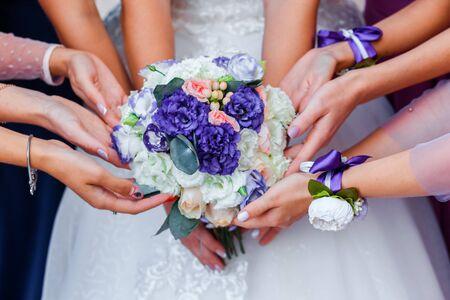 Bouquet de mariée entre les mains de la mariée. Beaucoup de mains de fille.