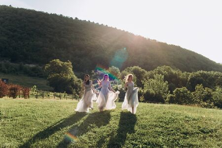 Bridesmaids in white dresses run on the green grass against the backdrop of the mountains. Foto de archivo