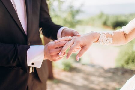 Wedding rings in the hands of the bride and groom.