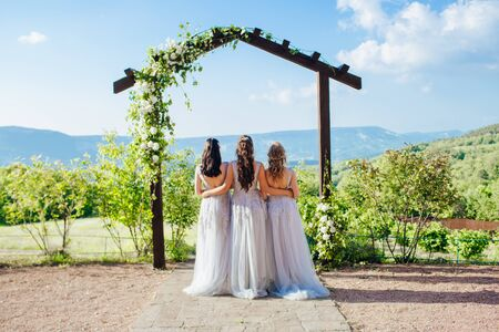 Bridesmaids in white dresses on the green grass against the backdrop of the mountains.