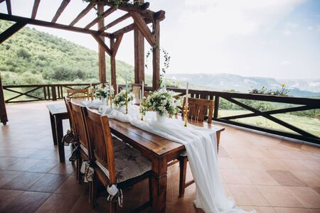 The wedding table decorated with fresh flowers is newlywed with a view of the mountains. Foto de archivo