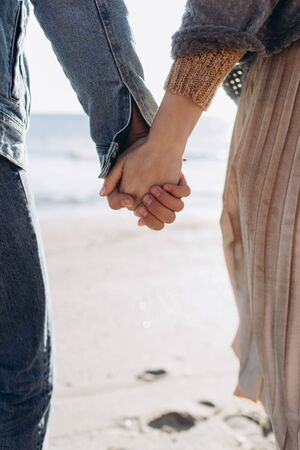 Hands of a couple against the background of the sea stretch to each other. Feelings. 版權商用圖片