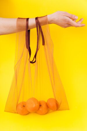Eco package on a bright yellow background. Zero waste and anti-plastic bag. Foto de archivo