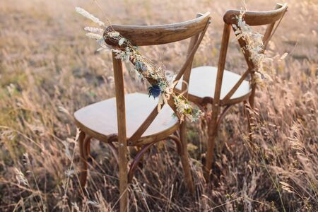 Decorated wedding chair for the newlyweds and guests. Wedding decor and Floristics.
