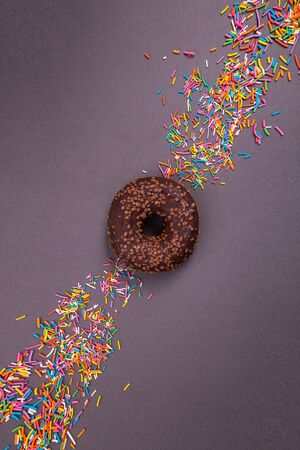Chocolate donut on a dark background. Abstraction and minimalism in food. Foto de archivo