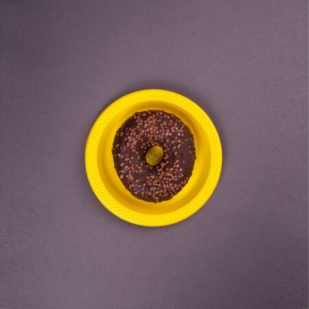 Chocolate donut on a yellow plate on a dark background. Abstraction and minimalism in food.