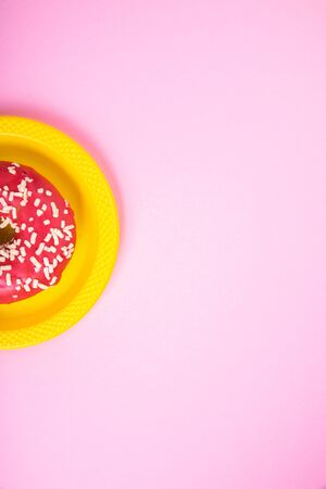 Pink donut on plate on a pink background. Sugar and obesity. Abstraction and minimalism. Foto de archivo