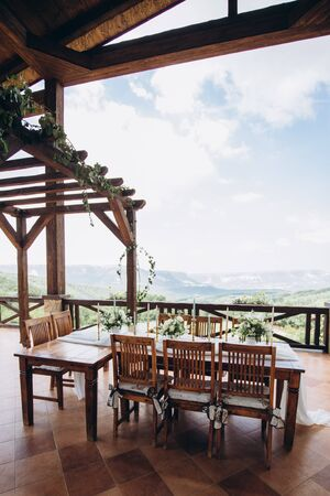 The wedding table decorated with fresh flowers is newlywed with a view of the mountains. Boho.