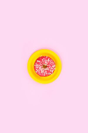 Pink donut on plate on a pink background. Sugar and obesity. Abstraction and minimalism. 版權商用圖片