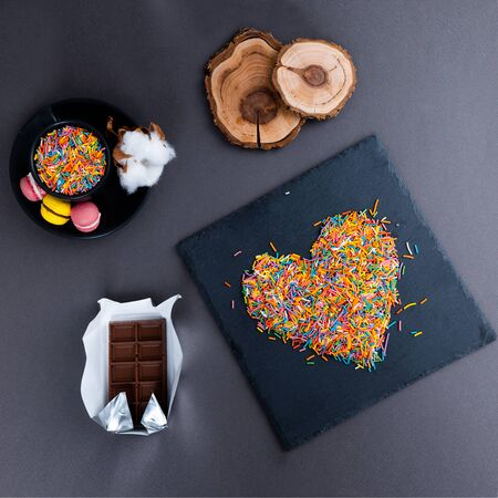 A layout of sweets, chocolate, hearts on a plate on a gray background. Minimal concept. Men's gift. Foto de archivo