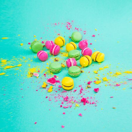 Bright small colored macaroons on a mint background. Colored sweets. Square. Foto de archivo