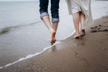 Two pairs of legs of lovers walk on the sand on the seashore.