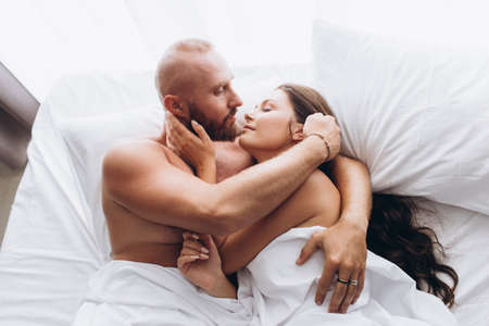 Couple is cuddling in bed. Traditional relationship.