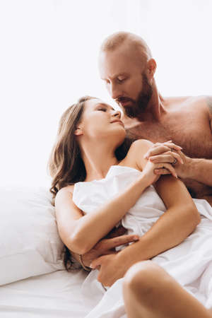 Loving couple in bed on white sheets.