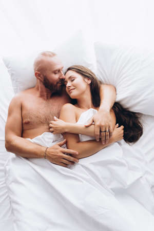 Loving couple in bed on white sheets. Stay at home.