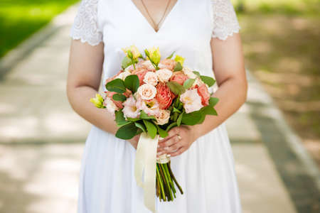 Classic bouquet of roses in the hands of the bride.