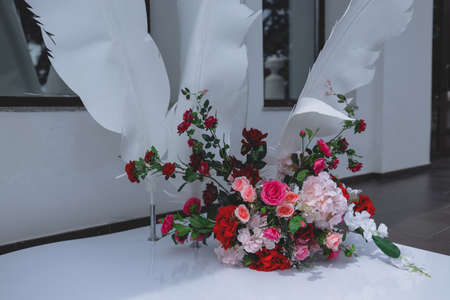 Wedding arch made of roses and decorative feathers.