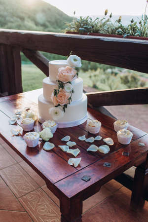 White wedding cake with flowers on a wooden table. Standard-Bild