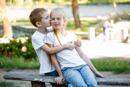 Cheerful children are kissing in the park on a green bench.