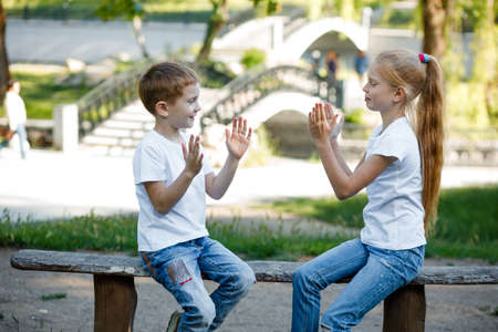 Cheerful children are playing in the park on a green bench.