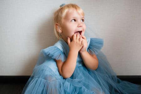 Little white girl in a blue dress laughs. Preschooler.