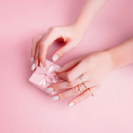 Gift for a girl on a pink background. Hands with manicure on a pink background.