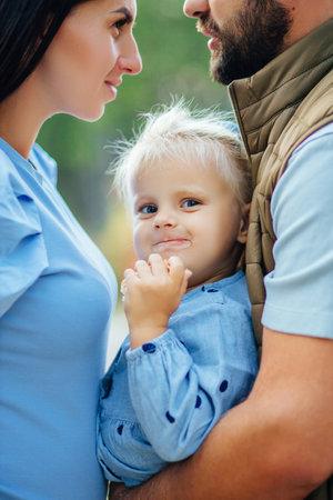 Little white girl in a white blue dress laughs in forest. Preschooler.