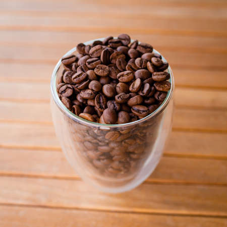 Coffee beans in a transparent glass glass. The smell of coffee.