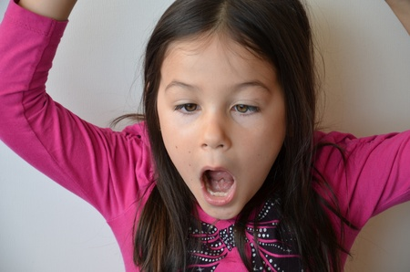 mouth  open: Cute little girl plays with her eyes to make a strange facial expression Stock Photo