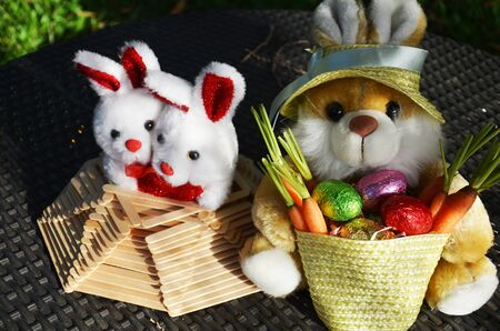 traditon: Soft toys rabbits with easter eggs and carrots in the basket