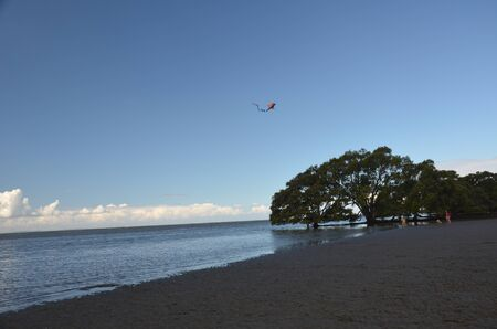 A flying kite in the sky  from far distance at Nudgee beach, Brisbane, Queensland Stock Photo