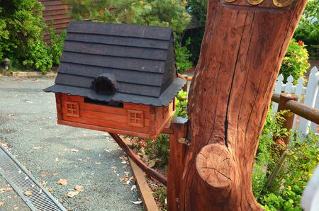 A small wooden house mail box attached with a log Stock Photo