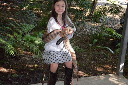 Little brave girl holds a big python in her arms