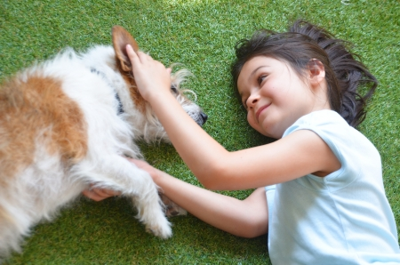 cutie: A cutie girl plays with a dog; Jack Russel terior