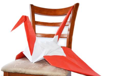 Giant crane made of a big piece of paper sitting on a chair
