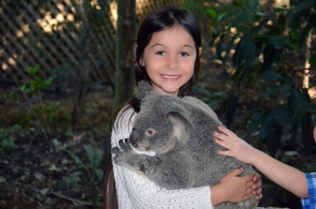 A little girl is holding a Koala in her arms photo
