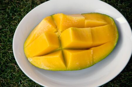 ripen: Halved ripen mango on a white plate Stock Photo