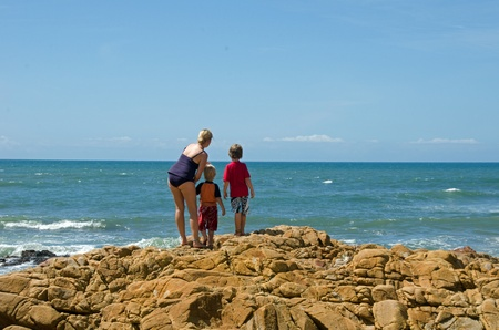 A family standing on the rocks looking out on the ocean Stock Photo