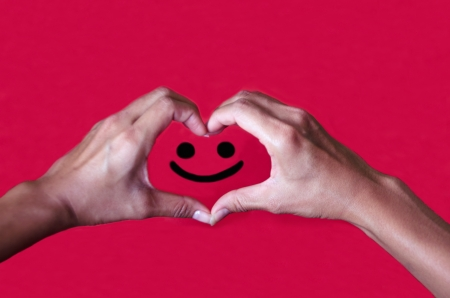 express feelings: Smiley face with a love heart shape created by hands