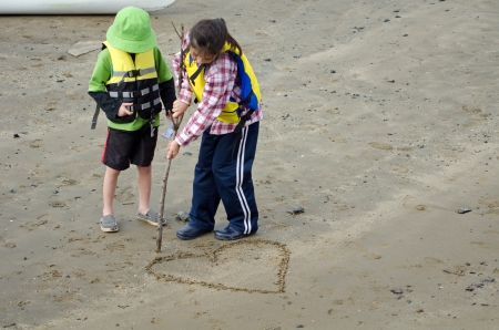 valentine s day beach: A boy is watching a girl drawing a love heart on the sand